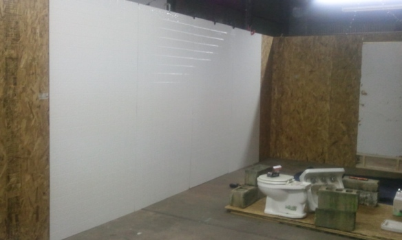 """Starting to install the tile. We used the 4'x8' sheets of shower tile. They're relatively easy to work with and cheap!"""